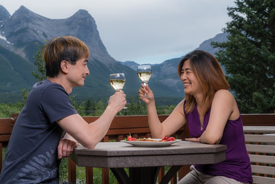 couple holding wine glasses and sitting at outdoor table