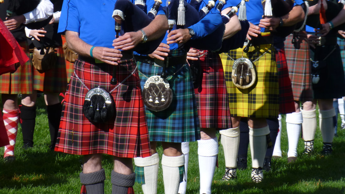 A large group of men wearing multicolored kilts